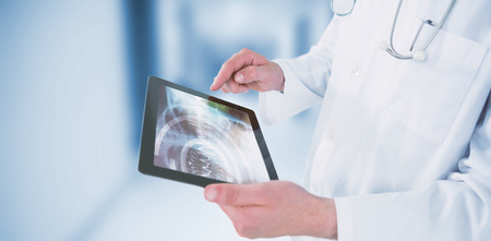 Doctor using digital tablet against dental equipment Stock Photo
