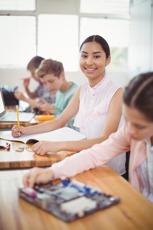 Retrato de la sonrisa de colegiala hacer la tarea en el aula en la escuela