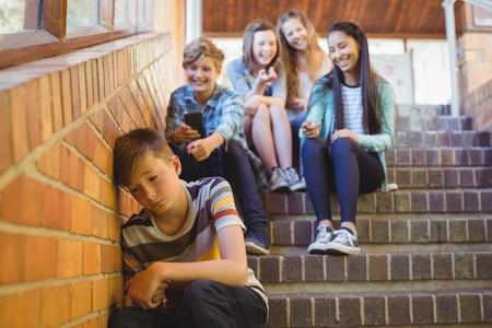 Gli amici della scuola mettono in pericolo un ragazzo triste nel corridoio scolastico a scuola Archivio Fotografico - 72332813