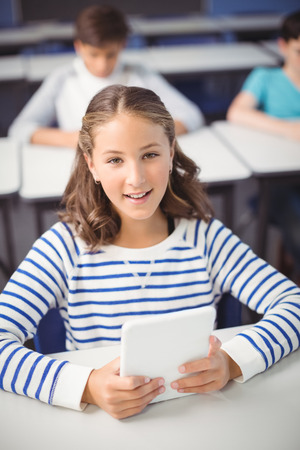 Portrait of student holding digital tablet in classroom at school