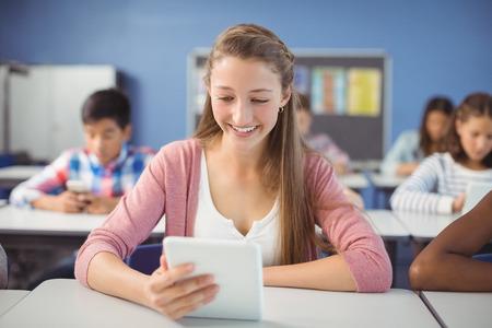 Student using digital tablet in classroom at school
