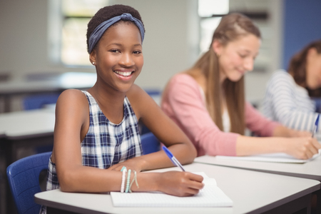 Portrait of student sitting at desk in classroom Stock Photo