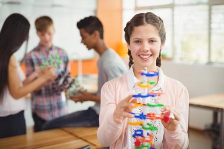 Retrato de colegiala sonriente examinando el modelo de molécula en el laboratorio
