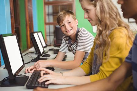 Estudiantes sonrientes que estudian en el aula de informática en la escuela