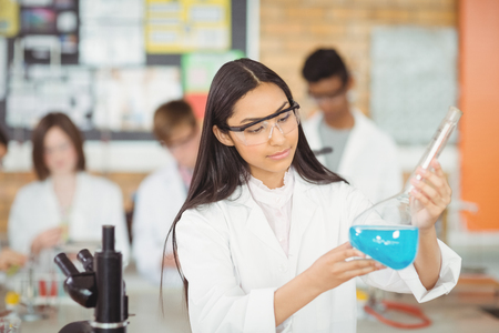 Estudiante atento haciendo un experimento químico en el laboratorio en la escuela Foto de archivo