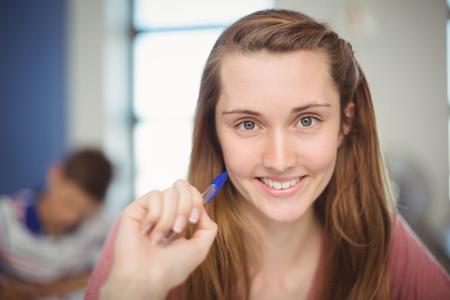 Retrato de niña sonriente haciendo la tarea en el aula en la escuela
