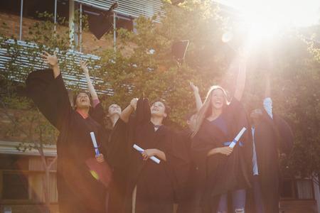master degree: Successful graduate school kids throwing mortarboard in air in campus at school