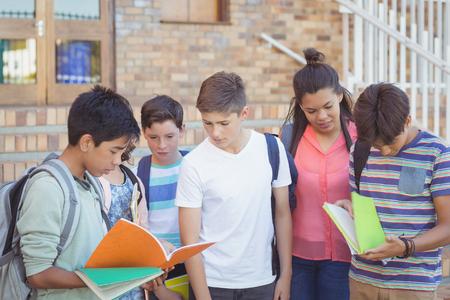 Niños de la escuela discutiendo sobre el libro de texto en el campus en la escuela