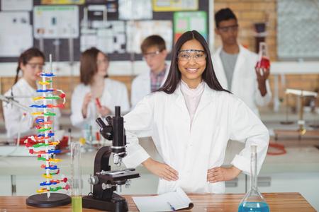 Retrato de niña de la escuela de pie con la mano en la cadera en el laboratorio en la escuela