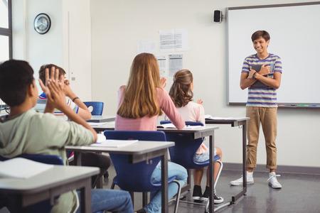 Schoolboy giving presentation in classroom at school