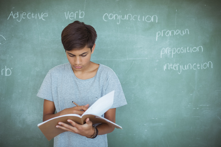 Attentive schoolboy reading book against chalkboard in classroom at school