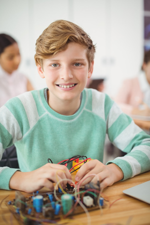 Portrait of smiling schoolboy working on electronic project in classroom