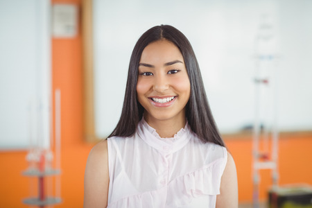 Portrait of smiling schoolgirl in classroom at school