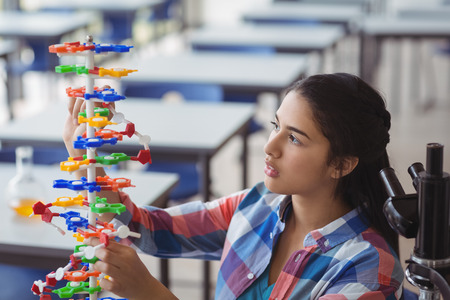 secondary school students: Attentive schoolgirl experimenting molecule model in laboratory at school