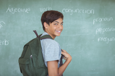 Portrait of schoolboy with backpack standing against chalkboard in classroom at school