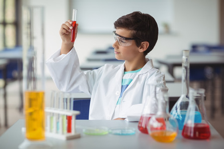 Attentive schoolboy doing a chemical experiment in laboratory at school
