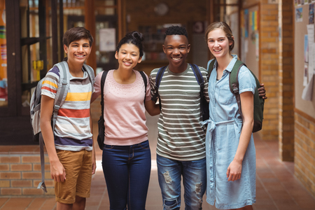 secondary school students: Portrait of happy students standing with arms around in corridor at school Stock Photo