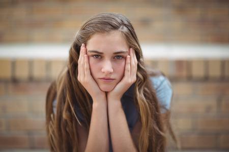 Portrait of sad schoolgirl sitting alone in campus at school