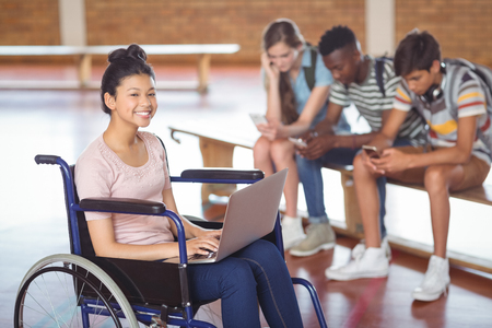 Portrait of disabled schoolgirl using laptop with classmates in background at school