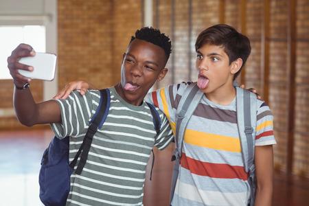 Happy schoolboys taking selfie on mobile phone in campus at school