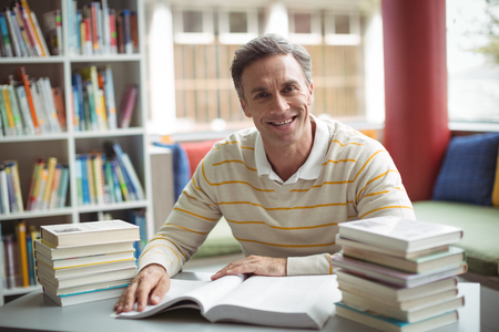 Portrait of school teacher reading book in library at school Stock Photo