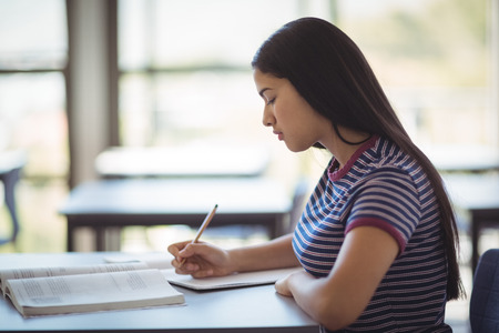 Attentive schoolgirl studying in classroom at school