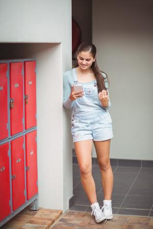 Schoolgirl using mobile phone in locker room at school