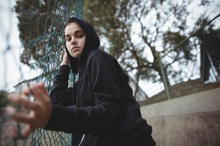 uneasy: Portrait of anxious teenage girl leaning on wire mesh fence at school campus
