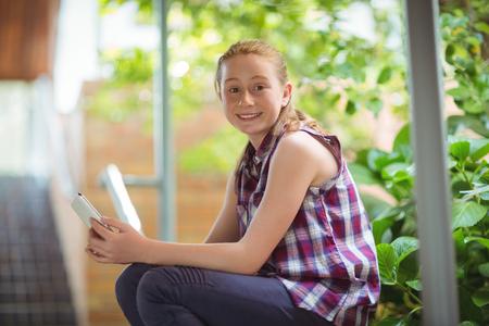Retrato de colegiala feliz con teléfono móvil en la escuela