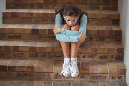 Sad schoolgirl sitting alone on staircase in school