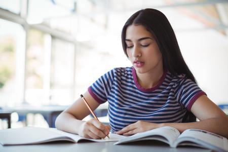 Attentive schoolgirl doing homework in classroom at school Stock Photo