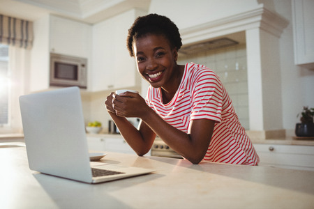 domicile: Portrait of woman using laptop while having coffee in kitchen at home Stock Photo