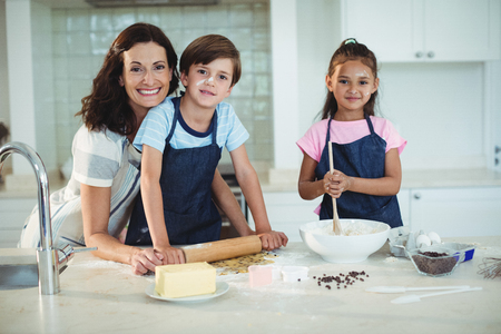 Portrait of mother and kids preparing cookies in kitchen at home