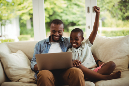 Father and son using laptop in living room at home Stock Photo
