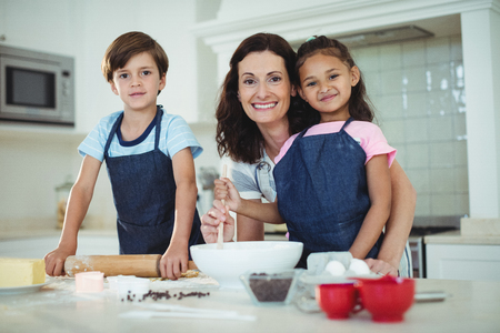 Portrait of mother and kids mixing the dough while preparing cookies in kitchen