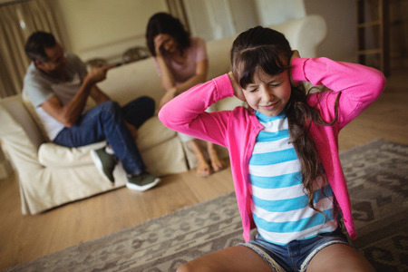 dysfunctional: Sad girl fed up of her parents arguing at home