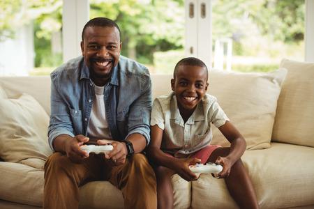niños jugando videojuegos: Retrato de padre e hijo jugando videojuego en la sala de estar en casa