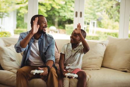 niños jugando videojuegos: Padre e hijo dar alta cinco el uno al otro mientras jugaba videojuego en casa