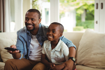 Son and father watching television at home