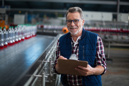 Portrait of smiling factory worker standing with a clipboard in drinks production plant Stock Photo