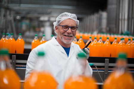 Portrait of smiling factory engineer standing near production line with walkie talkie in bottle factory Stock Photo