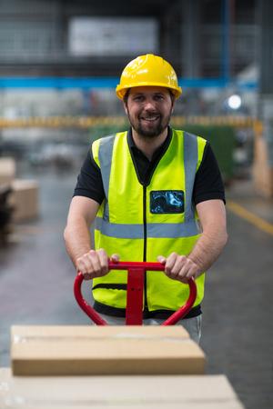 Porträt der lächelnden Fabrikarbeiter Wagen von Kartons in der Fabrik ziehen