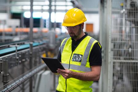 Fabrieksarbeider die een digitale tablet in fabriek gebruiken Stockfoto