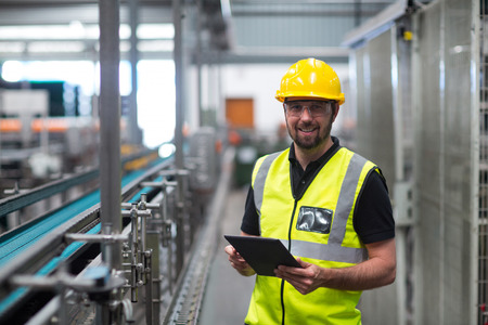 Portret van glimlachende fabrieksarbeider die een digitale tablet in fabriek gebruikt Stockfoto