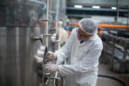 destilacion: Ingeniero de fábrica girando la rueda de control del tanque de almacenamiento en botella Foto de archivo