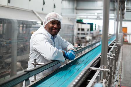 Portrait of factory engineer leaning on production line in drinks production plant Stock Photo - 72498625