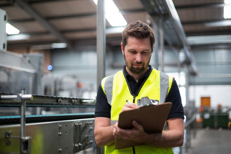 maintaining: Attentive factory worker writing on clipboard in factory