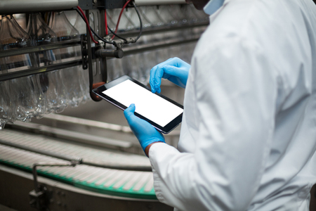 maintaining: Factory engineer using digital tablet in drinks production plant