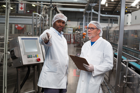 Two factory engineers discussing with each other in drinks production plant Stock Photo