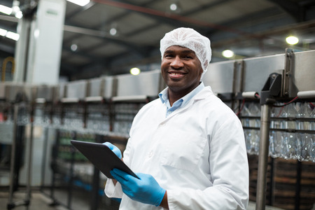 Portrait of factory engineer using digital tablet in drinks production plant